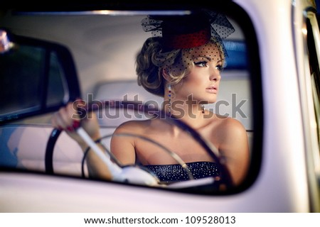 Portrait of beautiful sexy fashion girl model with bright makeup in retro style sitting in old car