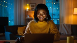 Portrait of Beautiful Smiling Black Girl Working on a Laptop while Sitting at Her Desk at Home. In the Evening Creative Woman Works on a Computer In Her Cozy Living Room.