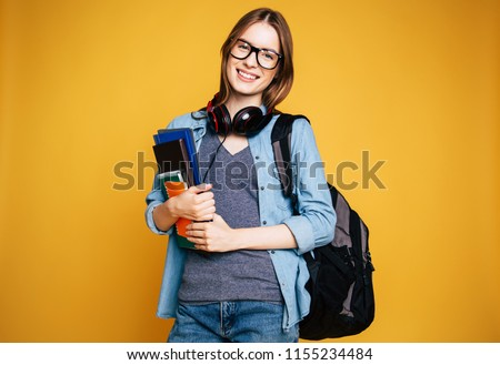 Portrait of beautiful smiling blonde woman. Young student on yellow background #1155234484