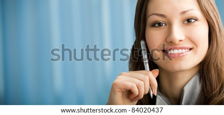 Portrait of beautiful smiling businesswoman with pen at office.To provide maximum quality, I have made this image by combination of two photos. You can use left part for slogan, big text or banner.