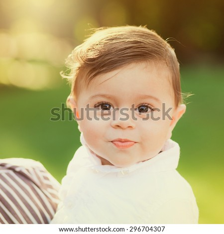Portrait of beautiful smiling cute baby boy. 8 month old little child playing outside in green summer or spring park.