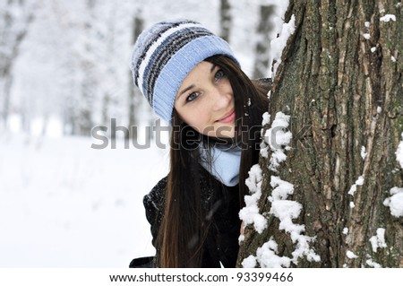 Portrait of beautiful smiling girl in snowy winter forest