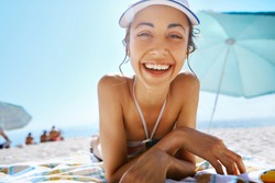 portrait of beautiful smiling happy woman tanning in bikini and white cap on sandy beach at summer. Model is relaxing lying down on white sand tropical getaway. Summer vacation concept.