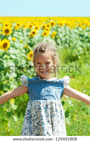 Portrait of beautiful smiling little girl, against background of sunflower field.
