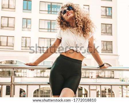 Portrait of beautiful smiling model with afro curls hairstyle dressed in summer hipster clothes.Sexy carefree girl posing in the street background. Trendy funny and positive woman having fun