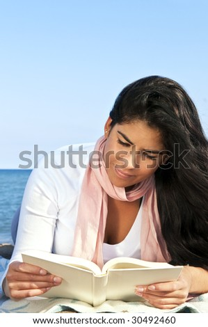Portrait of beautiful smiling native american girl reading book at beach - stock photo