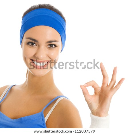 Portrait of beautiful smiling woman in fitness wear showing OK sign, isolated over white background