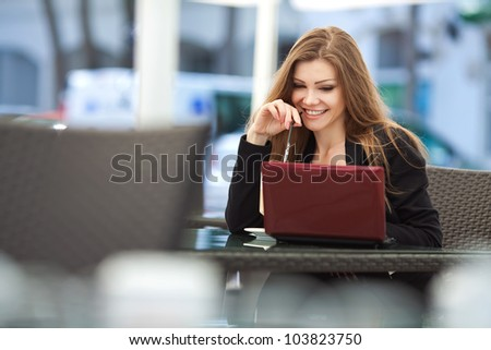 Portrait of beautiful smiling woman sitting in a cafe with laptop outdoor