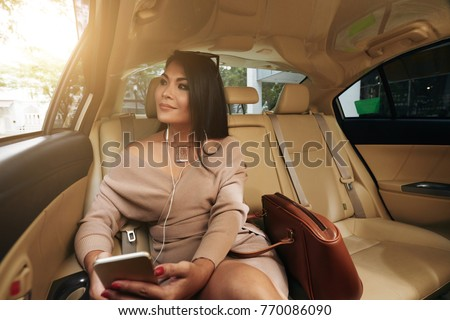 Portrait of beautiful smiling woman sitting on backseat in taxi #770086090