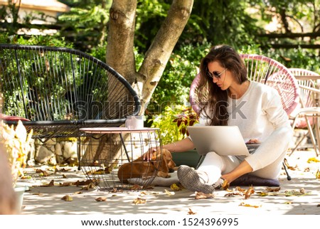Portrait Of Beautiful Smiling Woman Typing On Notebook Keyboard While Working Online Using Laptop Computer. Female Sitting On Terrace At Cafe With Her Pets And Pc On Her Knees. Business People Concept stock photo