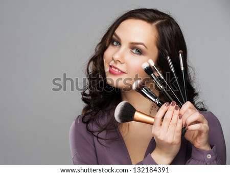Portrait of beautiful smiling woman with makeup brushes near her face