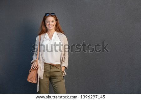Portrait of beautiful smiling woman with red hair looking at camera. Mature casual businesswoman feeling confident standing against grey wall, copy space. Business woman isolated on gray background.