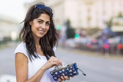 Portrait of Beautiful Smiling Woman with Wallet in the Hands on the Street