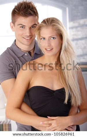 Portrait of beautiful smiling young couple standing, hugging, looking at camera.