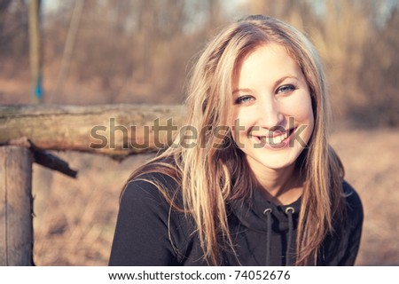 Portrait of beautiful smiling young woman at the park - Outdoor. Warm colors