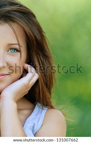 Portrait of beautiful smiling young woman close up, against background of summer green park.