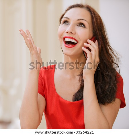 Portrait of beautiful smiling young woman in red dress which talks by mobile phone in big hall.