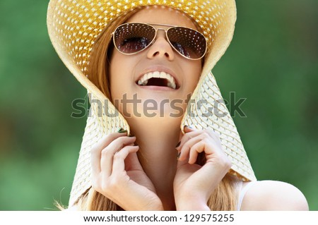 Portrait of beautiful smiling young woman in wide beach hat, against background of summer green park.