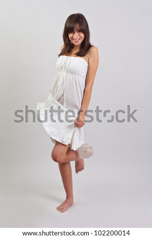 Portrait of beautiful smiling young woman standing in dress