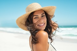 Portrait of beautiful smiling young woman wearing straw hat at beach with sea in background. Beauty fashion girl looking at camera at seaside. Carefree tanned woman walking on sand and laughing.