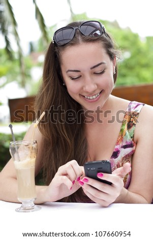 Portrait of beautiful smiling young woman, which talks by mobile phone