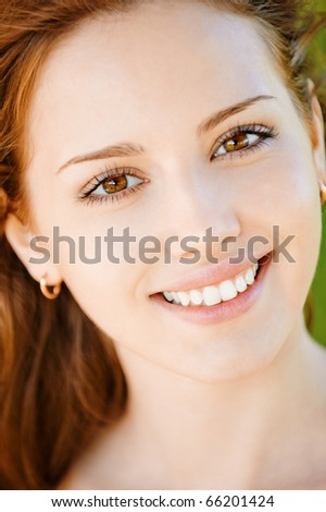 Portrait of beautiful smiling young woman with equal teeth close up.