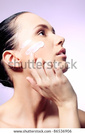Portrait of beautiful spa girl with cream on her face.