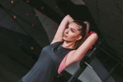 Portrait of beautiful sports woman lifting dumbbells from behind head while standing in dark gym. Athletic young girl in sports wear doing exercises for triceps with dumbbells. Muscle training in gym