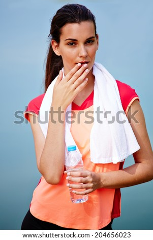 Portrait of beautiful sporty girl with bottle of water and towel, female runner resting after jog, fitness and healthy lifestyle concept