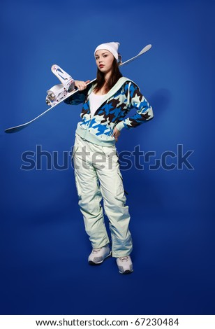 portrait of beautiful sporty girl with snowboards on blue