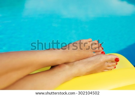 Portrait of beautiful tanned woman relaxing in swimming pool. Legs and hands close up. Creative gel polish red pedicure and manicure. Hot summer day and bright sunny light.