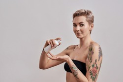 Portrait of beautiful tattooed woman with pierced nose and short hair holding plastic bottle with skin care product applying it on hand isolated over grey background. Horizontal shot