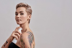 Portrait of beautiful tattooed woman with pierced nose and short hair holding plastic bottle with skin care product, body lotion applying it on shoulder isolated over grey background. Horizontal shot