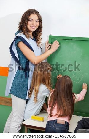 Portrait of beautiful teacher and children writing on chalkboard in classroom