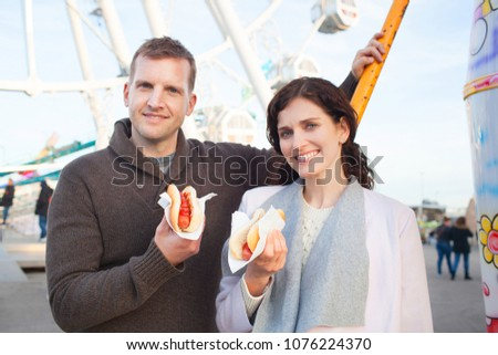 Portrait of beautiful tourist couple in fun fair, smiling together eating hot dog fast food outdoors. Man and woman holding junk food in amusement park, recreation leisure lifestyle.