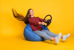 Portrait of beautiful trendy cheerful girl sitting in bag chair holding steering wheel wind blow hair isolated on bright yellow color background