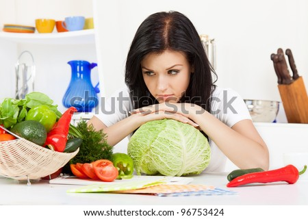 portrait of beautiful unhappy woman in the kitchen, sad lying on cabbage, sitting at the table