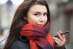 Portrait of beautiful white girl smoking vape pen.Pretty young woman smokes electronic cigarette device.Happy smoker female hold ecig gadget with glycerin eliquid.Bad habit background