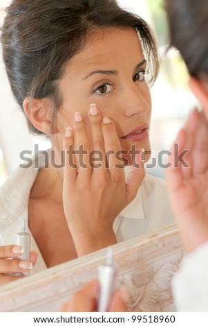 Portrait of beautiful woman applying anti-wrinkles cream