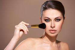 Portrait of beautiful woman applying cosmetic isolated on beige