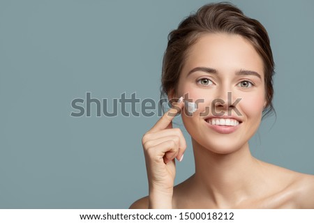 Portrait of beautiful woman applying cream on her face. #1500018212