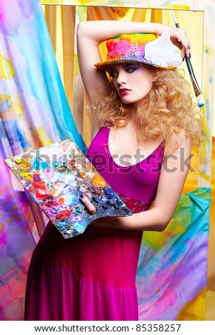 portrait of beautiful woman artist with paintbrush and palette standing in front of the easel with painted cloth on it