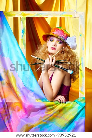 portrait of beautiful woman artist with paintbrushes standing behind the easel with painted cloth on it