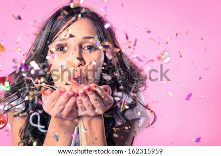 Portrait Of Beautiful Woman Blowing Confetti In The Air, Party New Years Eve Celebration On Pink Background