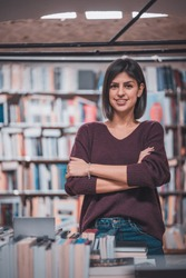 Portrait of beautiful woman bookshop owner. Successful independent businesswoman, owner of a book shop