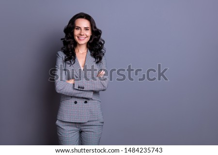 Portrait of beautiful woman crossing her hands wearing pants trousers isolated over gray background