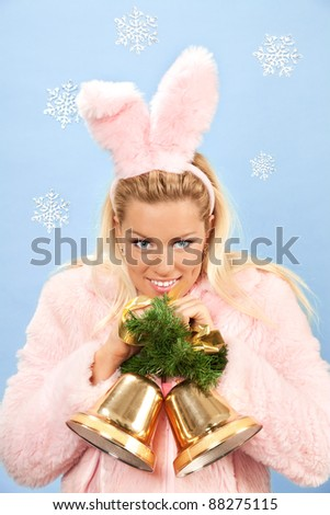 portrait of beautiful woman dressed as pink bunny with christmas bells