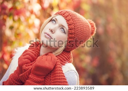 portrait of beautiful woman dressed in red knitted hat scarf and gloves against colorful leafy background