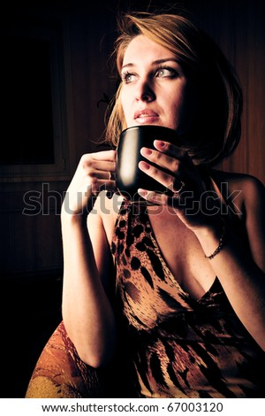 Portrait Of Beautiful Woman Drinking Coffee and magical wind blowing her hair