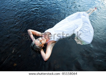 Portrait of beautiful woman enjoying silence and solitude floating in blue river in early summer morning